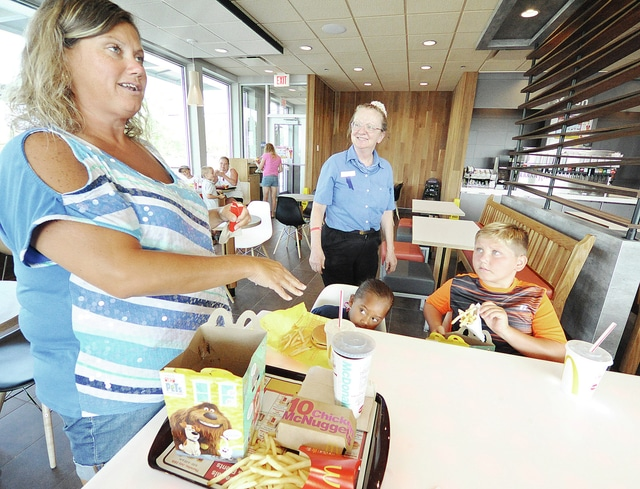 Anthony Weber | Civitas Media McDonald's Swing Manager Deb Westfall, a 39-year employee, visits with guests including Tori Broderick, of Piqua, and her children, Dotty Broderick, 4, and Seth Jacomet, 8, Tuesday during a silent opening of the new Scott Family McDonald's located at 995 E. Ash St., Piqua. Broderick was commenting on several features in the new store including the lighted table. A grand opening will be held at 10 a.m. Wednesday, and family fun events will be offered from 2-4 p.m., including prize giveaways. On Thursday, from 4-6 p.m., customers can enjoy a live show by Ronald McDonald and register to win a Pokemon gift basket. Daily deals will be offered over the next two weeks.