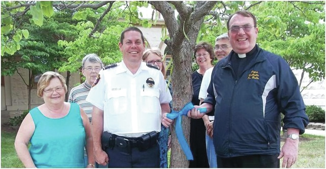 "Provided photo Showing support for Piqua's law enforcement officers and in answer to Piqua Public Library Director Jim Oda's recent challenge, St. Boniface & St. Mary Parishes recently decorated their property and Piqua Catholic School's with blue ribbons. Echoing Oda, Fr. Tom Bolte, pastor of the parishes, said, ""The police do a great job, and we support and thank them for what they do!"" Pictured are Piqua Chief of Police Bruce Jamison, Fr. Tom Bolte, and members of the parish staff."