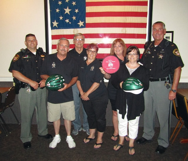 Provided photo Troy Elks officers are pictured with a couple of the bicycle helmets and items purchased through a grant they have given to the Miami County Sheriff's Office. Chief Deputy Dave Duchak and other sheriff's office representatives also are in the photo.