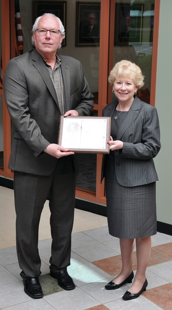 Provided photo RT Industries CEO Blair Brubaker receives an award from Dr. Nancy Luce.