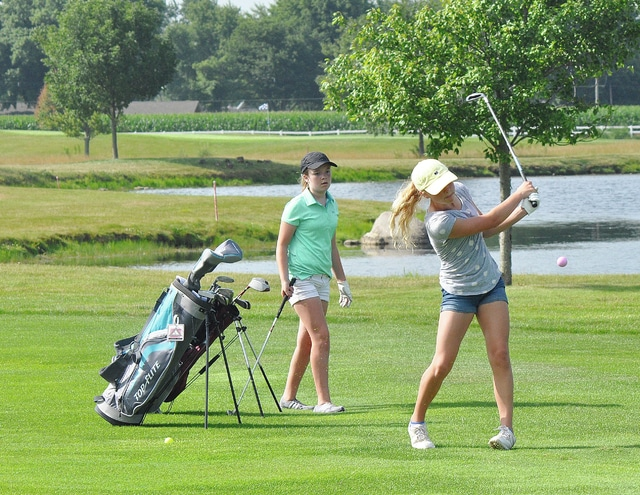 Rob Kiser/Call Photo Lauren York hits a shot to eighth green at the Echo Hills Junior Camp as Madison Supinger looks on,