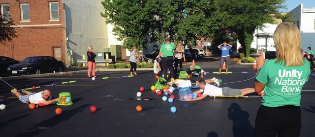 Mike Ullery | Daily Call Unity National Bank employees compete to capture water balloons during an Associate Appreciation Week event to raise money for the United Way at the bank's main office in downtown Piqua on Tuesday morning.