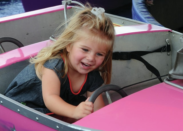 Mike Ullery | Daily Call Two-year-old Jaelynn Line of Troy drives her boat at the Miami County Fair on Saturday.