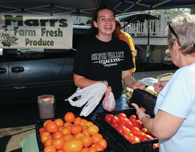 Mike Ullery | Daily Call Roxana Chesser of Piqua purchases fresh tomatoes from Allie Popp of Marrs Farm Fresh Produce during Thursday's Piqua Farmers Market. There are two more chances to visit this year's Piqua Farmers Market. September 1 was originally slated to be the final week for 2016 but vendors requested one more week, so the final day for this year will be September 8.
