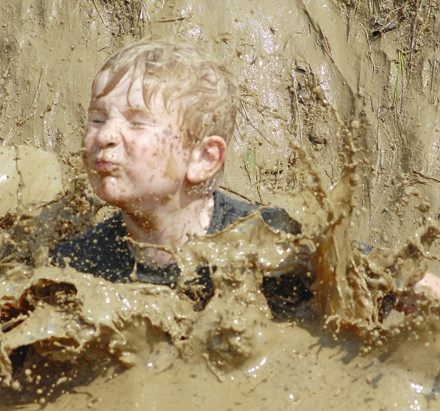 "Anthony Weber | Civitas Media Campers of ""Bee"" Bonita Pierce's 6-and-7-year-old group, including Owen Poeppleman, take the plunge into a mud pit during the Eco-Splorers Water Week through the Miami County Park District Tuesday at Garbry Big Woods Reserve near Fletcher. Participants of Eco-Splorers explored the pond and creeks as well as crafted a boat to race during the camp. Friday is family day for campers and their families and is the finale to water week and Eco-Splorers for the summer."