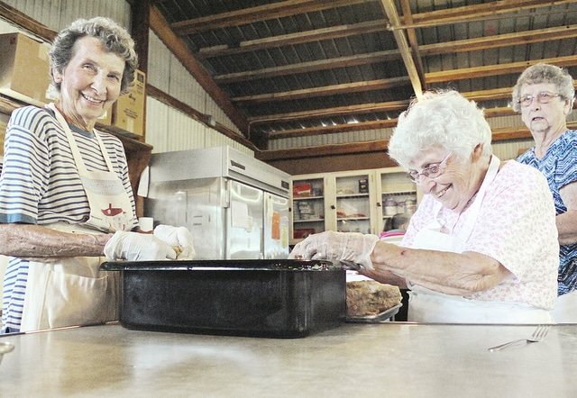Anthony Weber | Troy Daily News Sisters Amy Eidemiller, 90, and Doris Beeson, 97, work on pulling pork apart recently for Cove Spring Grange in preparation of a Monday special at the Miami County Fair. The pair have been a part of Cove Spring Grange for more than 60 years.