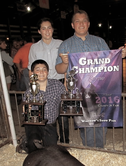 Jack Shell, 15, of Covington (kneeling) exhibited the Junior Fair Grand Champion Market Barrow on Tuesday. He is pictured with his sister, Carly, and brother, Jesse.