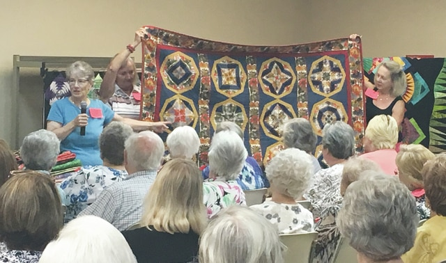 Sam Wildow | Daily Call Linda Thoma Cooper (front left) discusses her kaleidoscope quilt during the monthly luncheon at the YWCA on Wednesday.