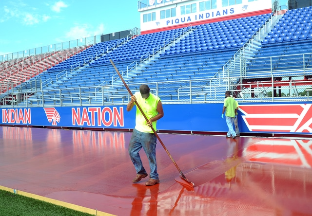 Mike Ullery | Daily Call Piqua High School is getting a new all-weather surface for their track at Alexander Stadium/Purk Field. Crews were applying a second layer of polyurethane on Thursday.