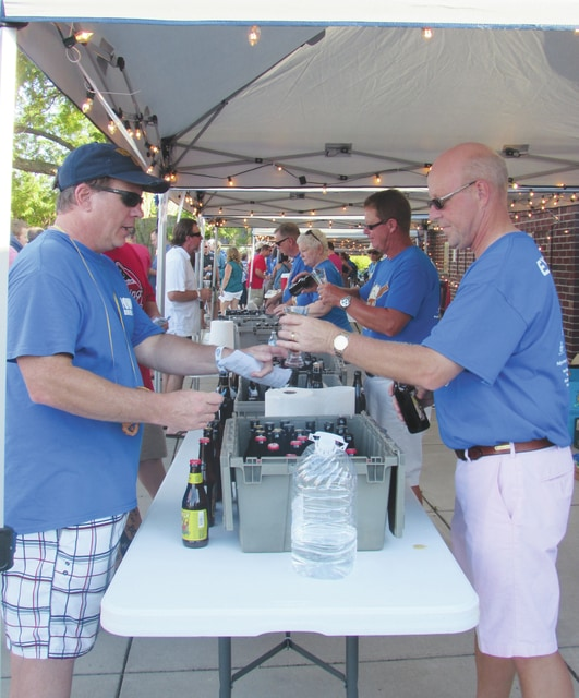 Sam Wildow | Daily Call Brett Baumeister (front right), president of Unity National Bank, and Rob Bornhorst (back right), SFO of Buckeye Insurance, pour beer for attendees at the third annual Down a River, Down a Beer event on Saturday in Lock 9 Park.
