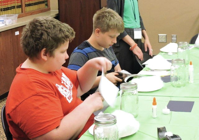 Provided photo Teens take part in the teen summer program at the Piqua Public Library, crafting ghosts in a jar.