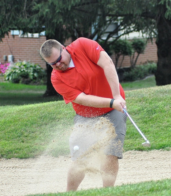 Rob Kiser/Call Photo Andy Arp blasts out of a bunker on the ninth hole Saturday at Piqua Country Club.