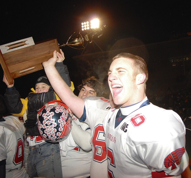 James E. Mahan/Call File Photo Bryant Fox (6) helps a young Alex Nees hold up the state championship trophy in 2006 after the Indians defeated Pickerington Central.