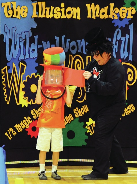 Mike Ullery | Daily Call Trent Lucas, a second-grader at Springcreek Primary Elementary School, left, assists The Illusion Maker, aka David James of Scranton, Pa., with one of his magic tricks during a performance at the school on Tuesday.
