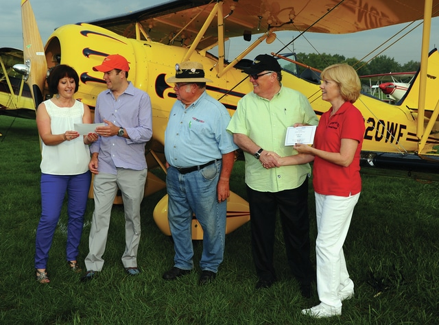 Mike Ullery   Civitas Media Nancy Royer, far left, and Gretchen Hawk, far right, of the WACO Air Museum in Troy, present Jordan Jaffe and Doug Jaffe, with Lifetime Memberships to the WACO Air Museum on Saturday. The Jaffe's, who are from Austin, TX, donated a 2004 WACO Classic YMF-F5C, 3-seat aircraft to the WACO Air Museum on Friday evening. Pictured in the center is Troy resident Bob Wagner, who has worked as a test pilot for WACO Classic Aircraft for a number of years and is also a well-known air show performer.