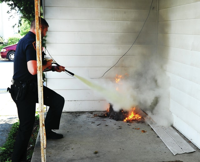 Mike Ullery | Daily Call Officer Todd Voskuhl extinguishes a fire on the porch of a home at the intersection of Park Ave. and Madison Ave. on Wednesday afternoon. Piqua Fire Department was dispatched the former Chick House building on the report of smoke coming from the roof around 4 p.m. Police officers arrived first and discovered burning material on the porch. Officer Voskuhl, armed with a fire extinguisher, doused the blaze before it could spread. Piqua firefighters made entry in to an upstairs apartment to check out the smoke that was still coming from under the eves of the building. A fire investigator from the Piqua Fire Department is looking into the cause of the fire. There were no injuries.
