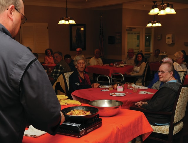 Mike Ullery | Daily Call Chef Ben Davis creates a Bananas Foster dessert as residents of Piqua Manor Nursing Home watch at the residence on Wednesday.
