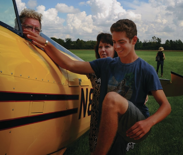 Mike Ullery   Daily Call Dylan Warren, 15, of Piqua, climbs aboard the WACO Air Museum and Aviation Learning Center's WACO Classic at WACO Field. Warren, a volunteer at WACO, had the honor of taking the first Young Eagles flight ever given aboard WACO's aircraft that was received dure to a generous donation by Doug and Jordan Jaffe of Austin, Texas. Flying Warren on his Young Eagles flight is legendary air show pilot Bob Wagner, of Troy. Assisting Warren in boarding the airplane is WACO Aviation Learning Center Director Nancy Royer.