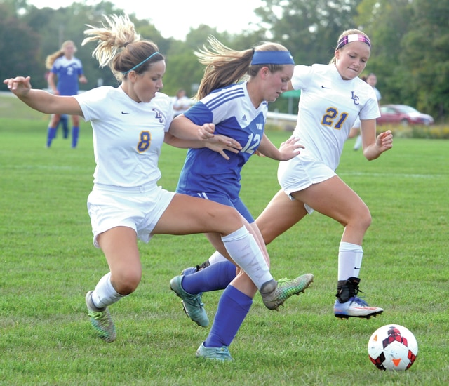 Mike Ullery | Daily Call Lehman's Molly Safreed, 8, and Grace Olding, 21, work against Miami East's Whitley Gross, 12.