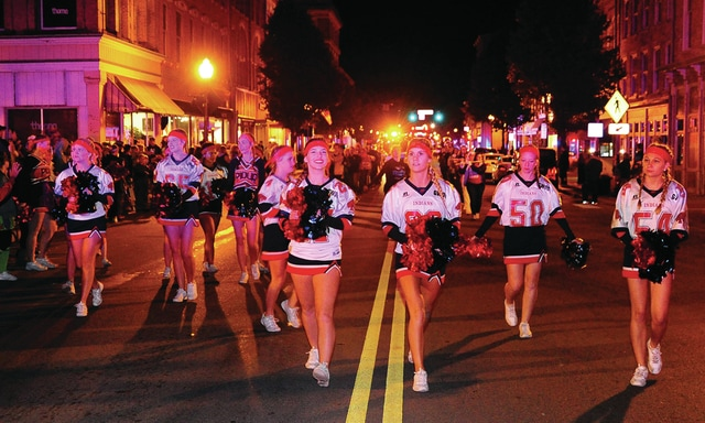 Mike Ullery | Daily Call The Piqua Indians cheerleaders lead the football team to the gazebo in downtown Piqua on Wednesday night to a large pep rally to get fans fired up for tonight's big game against Troy.