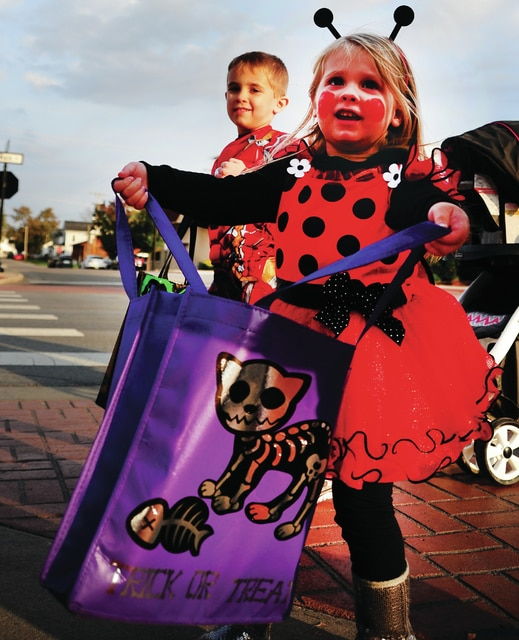 Mike Ullery | Daily Call Madilyn Tackett, 2, and her brother Gaven, 5, Trick-or-Treat in downtown Piqua on Wednesday evening during the annual Mainstreet Piqua Halloween event.