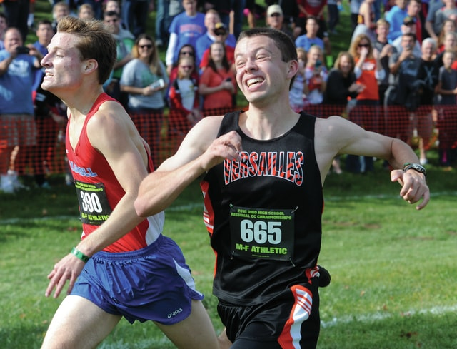 Mike Ullery | Daily Call Versailles' Joe Spitzer(665) stretches to edge Carroll's Mike Laughlin at the finish line and win the Division II regional race Saturday at Troy.