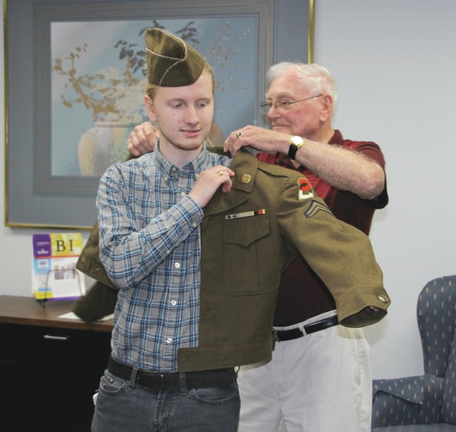 Provided photo Edison State honor student Riley Poland tries on veteran Weldon Oakley's office jacket and hat from the Korean War.