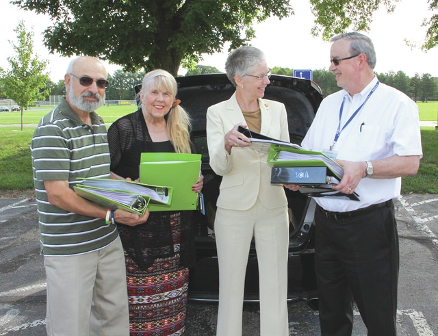 Provided photo Edison State faculty member Dr. Vivian Blevins (second from left), along with Edison State President Dr. Doreen Larson, present the collection of veteran stories to Jim Oda, director of the Piqua Public Library (right) and Carl DeSantis, board member of the Miami Valley Veterans Museum in Troy.