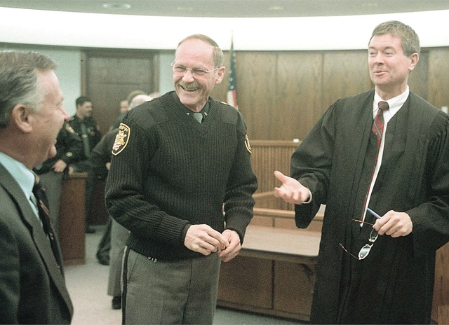 Anthony Weber | Troy Daily News Miami County Commissioner Richard Adams and Miami County Common Pleas Court Judge Robert Lindeman congratulate Sheriff Charles Cox after being sworn in for another term in 2000.