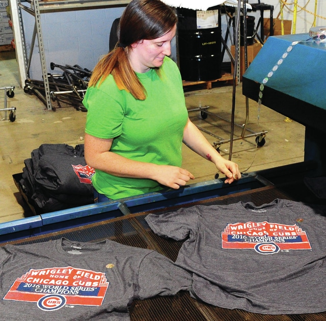 Mike Ullery | Daily Call Ayrie Schwartzengraber of Piqua places Licensed Authentic stickers on Chicago Cubs 2016 World Champions t-shirts at Atlantis Sportswear in Piqua on Tuesday morning. Atlantis is one of the major producers of licensed sports apparel in the country. The t-shirts will be transported to a Fanatics.com warehouse where they will be available for online purchase.