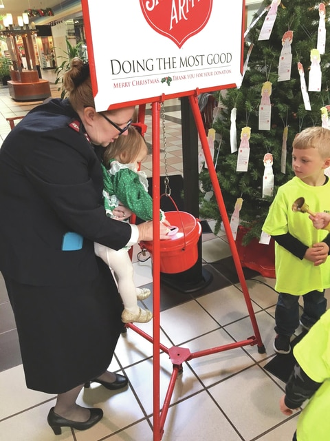 Provided photo Major Jody Kramer helps Rylee Starnes place the first donation of the Salvation Army of Piqua's Red Kettle Campaign 2016 during the campaign kickoff Friday at the Miami Valley Centre Mall. The campaign, which runs through Dec. 24, has a goal of $45,000.