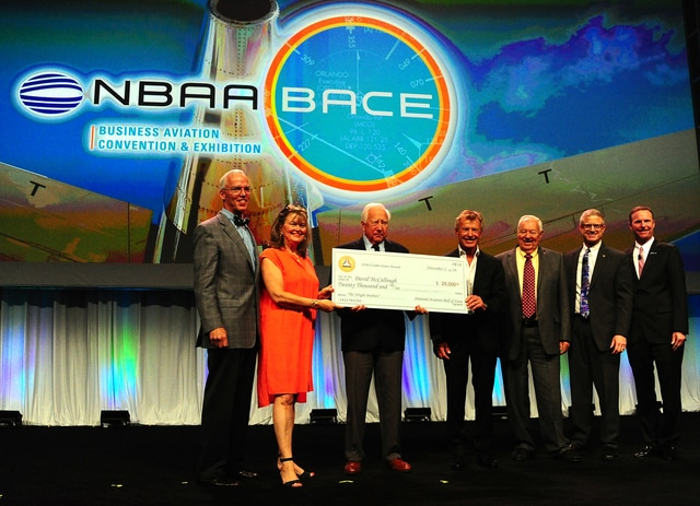 Mike Ullery | Daily Call Best-selling author David McCullough, center receives a check for $20,000 from Amanda Wright-Lane, great grand-niece of Wilber and Orville Wright during the Wednesday general session at NBAA in Orlando. McCullough won the 2016 National Aviation Hall of Fame Combs-Gates Award for his book <em>The Wright Brothers</em>. Front left to right in the photo are, Bill Harris, president of the National Aviation Hall of Fame, Wright-Lane, McCullough, NAHF enshrinees Sean Tucker and Clay Lacy, NAHF Enshrinement Director Ron Kaplan, and NBAA President Ed Bolin.