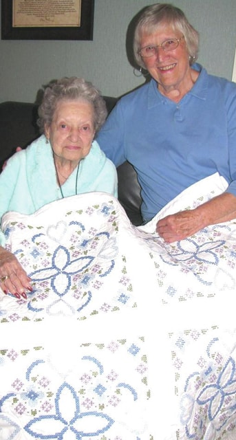 Provided photo Displaying this year's quilt are Jo Gast and Juanita Ventura. Gast, a longtime member of St. Boniface Parish, chose the pattern and completed the first block. Ventura organized the volunteers who completed the remaining blocks.