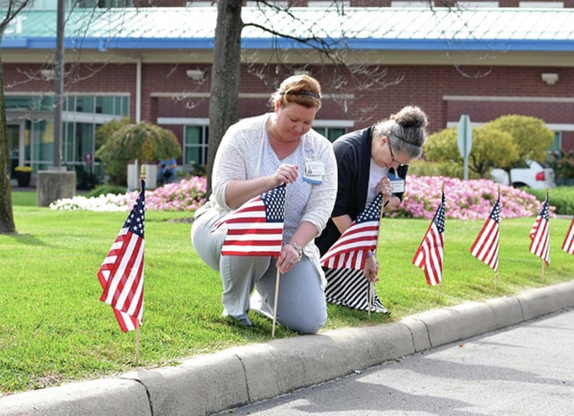Provided photo UVMC Future Leaders chair Wendy Fullerton (left) and co-chair Liz Schwartz place memorial flags along the hospital main driveway in honor of veterans. The flags project was sponsored by the Future Leaders group and hospital administration.