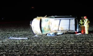 Troy firefighters examine the wreckage of a minivan that crashed on Washington Road on Friday evening.