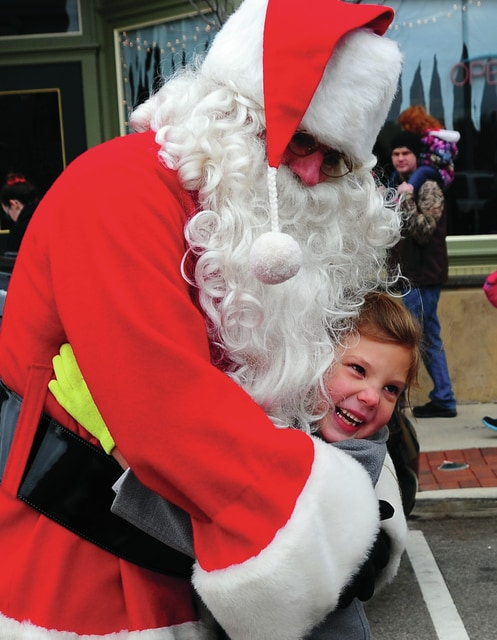 Mike Ullery | Daily Call MacKenzie Grear, 7, of Piqua waited all year for a hug from Santa Claus as she rushed to him in front of the Piqua Public Library on Saturday.
