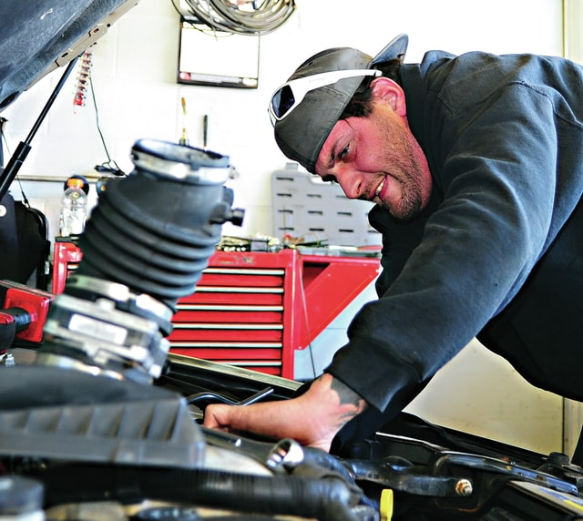Mike Ullery | Daily Call Matthew Pisano of Piqua Express Care works on a car in their shop on Friday.