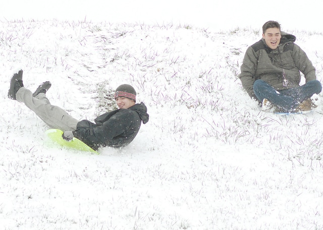 Anthony Weber | Troy Daily News Danny Theders of Cincinnati, left, and Blake Tubera of Arizona, took some time to sled down the levee while being away from class Tuesday in Troy. Both are welding students at the Hobart Institute of Welding Technology, and according to Tubera, it is his first time living in an area where there is snow.
