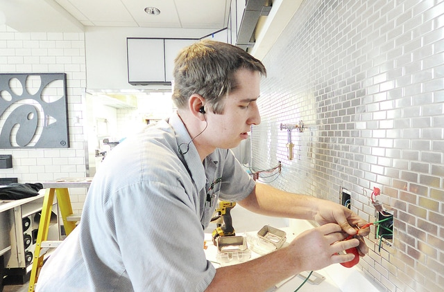 Anthony Weber | Troy Daily News Electricians from B Electric Inc., including Evan Bowman of Covington, work on electrical work around the serving area at the new Chick-fil-A restaurant in front of Meijer in Troy.