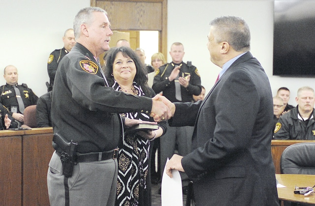 Anthony Weber | Troy Daily News Newly elected Miami County Sheriff Dave Duchak shakes hands with Miami County Prosecutor Tony Kendell inside Judge Christopher Gee's Common Pleas courtroom at the Miami County Safety Building. Duchak was accompanied by his wife, Sheri, during the official oath of office Wednesday in Troy.