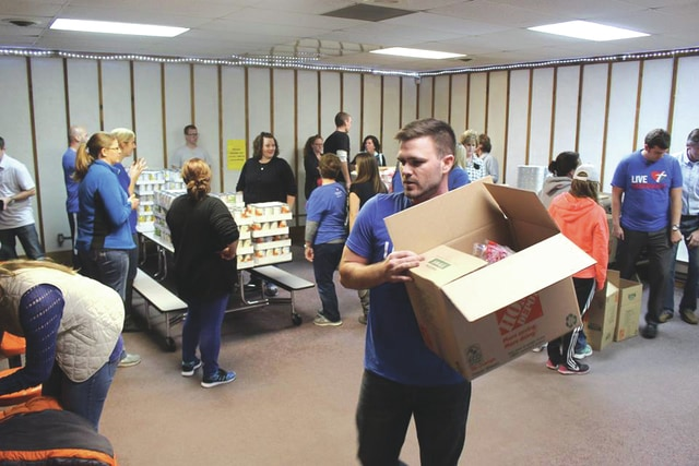 Provided photo Volunteers prepare to pack meal kits for distribution to needy families as part of a Western Ohio Thrivent community project.
