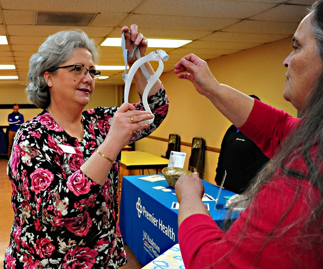 Mike Ullery | Daily Call Piqua YWCA Executive Director Leesa Baker, left, learns about a sleep disorders mask from a UVMC representative during Thursday's open house at the Piqua YWCA for the facility's new Fitness Center.