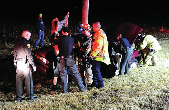 Mike Ullery | Daily Call Miami County deputies and firefighters and paramedics from Troy Fire Department check out the victim of a single vehicle crash on State Route 41 near Washington Road on Wednesday evening.