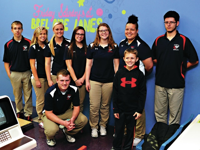 Mike Ullery | Daily Call Keidin Pratt, 9, poses with the Piqua High School bowling team seniors at Brel Aire Lanes on Thursday.