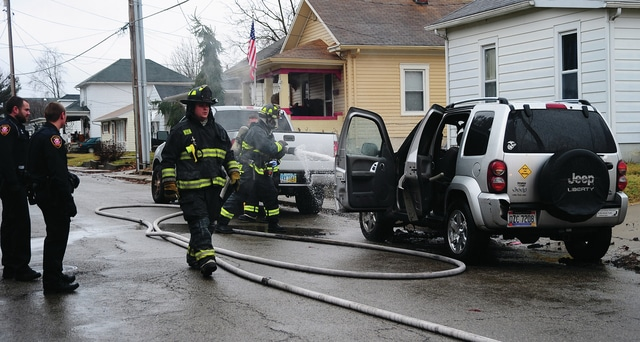 Mike Ullery | Daily Call Piqua police officers stand by as firefighters extinguish a fire in an SUV in the 900 block of Young Street on Monday afternoon.