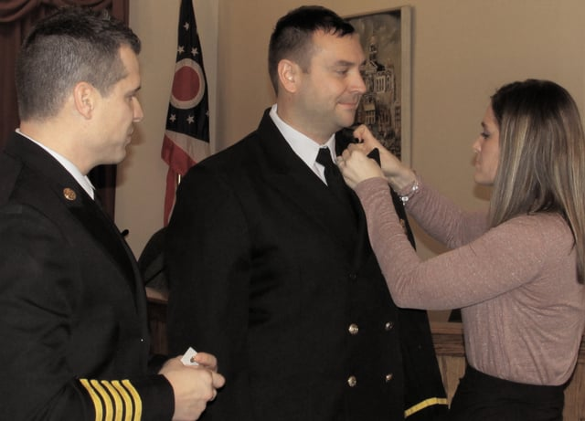 From left, Chief Matthew Simmons watches as his brother, Aaron, receives his lieutenant pins from his wife, Nicole, in a ceremony Wednesday at City Hall. Lt. Simmons will oversee staff training and other duties for the Troy Fire Department.