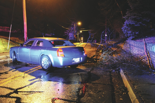 Mike Ullery   Daily Call A car struck tree limbs as they fell across Park Avenue in Piqua on Tuesday. High winds and heavy rain swept through the county on Tuesday night, causing damage and power outages.