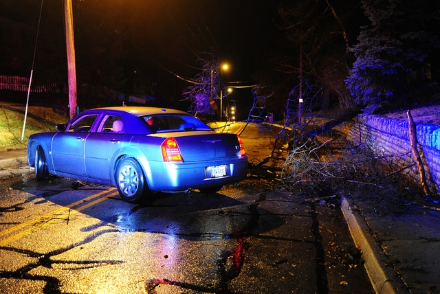 A car struck tree limbs as they fell across Park Ave. in Piqua on Tuesday.