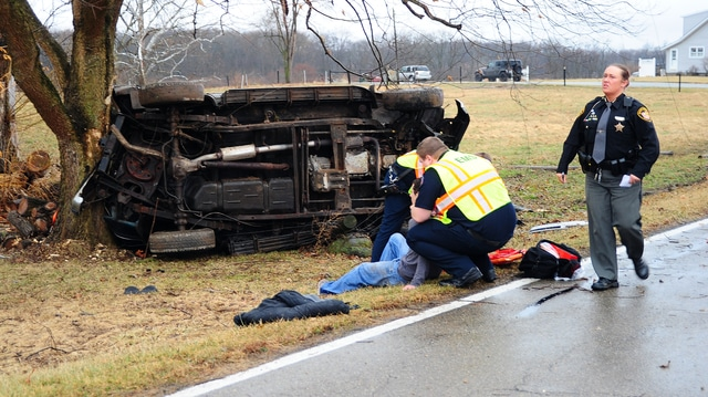 Mike Ullery | Daily Call Miami County Sheriff's Deputies along with medics and firefighters from the Troy Fire Department work the scene of a one-vehicle crash on Piqua-Troy Road on Tuesday afternoon.
