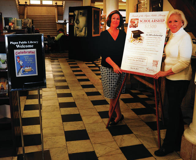 Mike Ullery | Daily Call Julia Benkert, left, and Joyce Jenkins display signage related to the Friends of the Piqua Public Library Scholarship to be given away by the group.